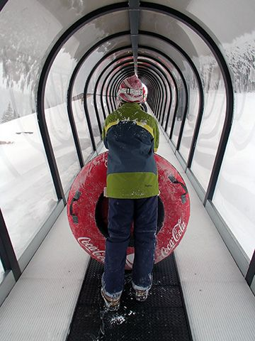 Riding the covered conveyor belt back up the hill at Coca-Cola tubing at Winter Park Resort. #VisitGrandCounty