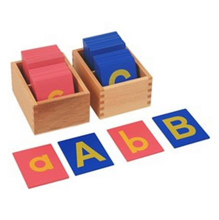 Letters cut out in fine sandpaper and mounted on card. The vowels are on blue wooden boards and the consonants are on pink wooden boards. It includes 26 sandpa