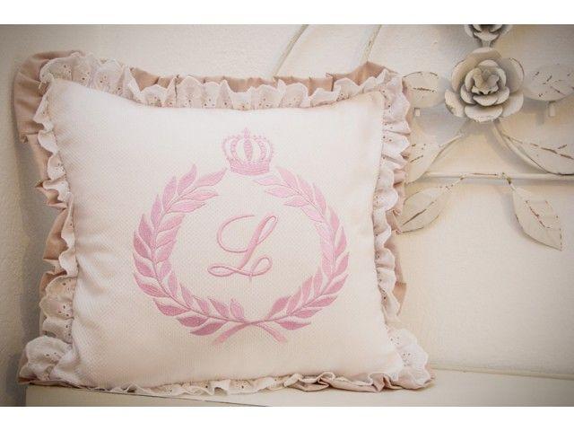 Almofada decorativa revestida em piquet branco, bordada com a inicial do nome do bebê, a coroa e brasão na cor rosa