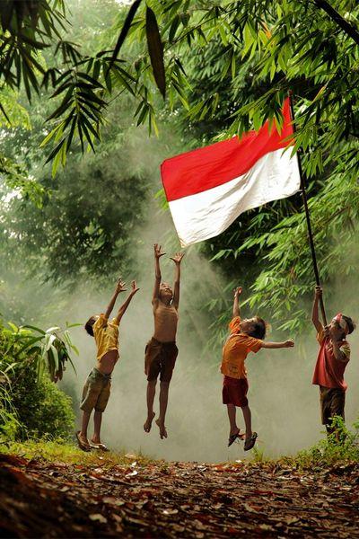 Fieri di essere indonesiani - Fotografia di Nelly Putnam Ci sono molte celebrazioni nel villaggio durante il giorno dell'indipendenza indonesiana. Dei ragazzi giocano con la bandiera cercando di saltare per arrivare a toccarla...
