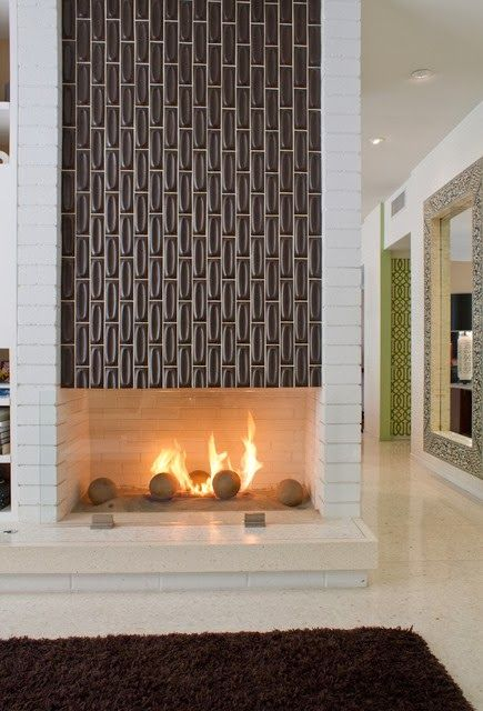 A mid-century modern, two-sided fireplace featuring tile by Heath Ceramics. Image via Apartment Therapy.