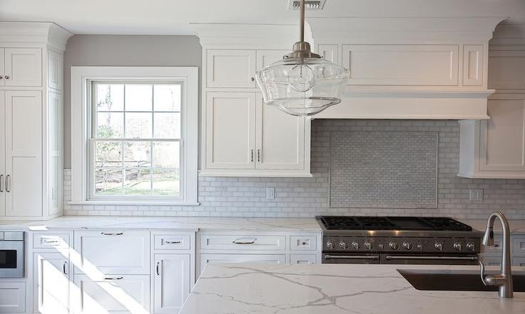 In a beautiful all white transitional kitchen, a clear glass schoolhouse pendant hangs above a Calcutta marble kitchen island countertop fitted with an undermount sink and a satin nickel gooseneck faucet.