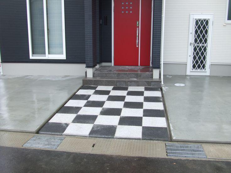 洋風の家に、チェスボードのように平板を敷いたアプローチ。
