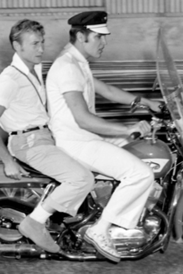 "Elvis with Nick Adams on one of his first Harley Davidsons and wearing his ""Star"" cap."