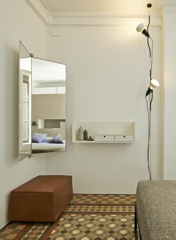 Ristrutturazione di un appartamento a Barcellona. Un angolo della camera padronale è allestito come un moderno boudoir: specchio a libro 'Book' di De Padova sopra al pouf 'Doda' di Molteni & C. Il mobile da appoggio a parete 'Fortepiano' è uno dei sistemi di Molteni & C. Un classico di leggerezza la lampada appesa 'Parentesi', disegnata nel 1971 da Achille Castiglioni e Pio Manzù per Flos. #interiors #design #mirror #bedroom #floorlamp #home