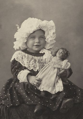 Child with what appears to be a wax head doll