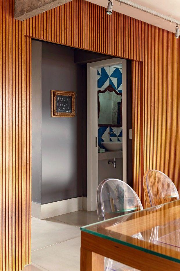 O painel ripado de freijó, feito pela JR Marcenaria Design, separa a área social da cozinha e do lavabo. Lousa com moldura dourada, da Coisas da Doris (Foto: Edu Castello/Editora Globo)