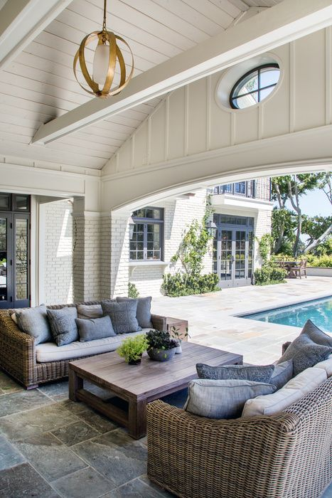 Beautiful covered patio featuring vaulted ceilings, wicker sofas, a teak coffee table and a built-in pool | Dana Benson Construction