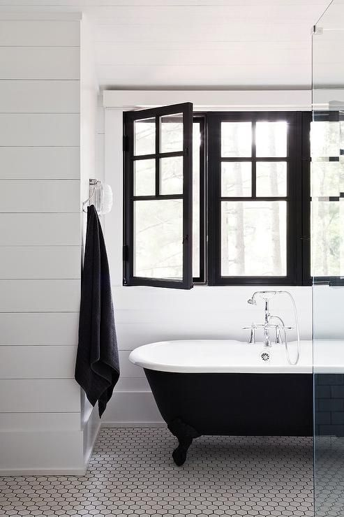 Black and white cottage style kids' bathroom features walls clad in white shiplap trim framing three black framed windows situated over a black clawfoot bathtub on white hex tiled floors finished with black grout.