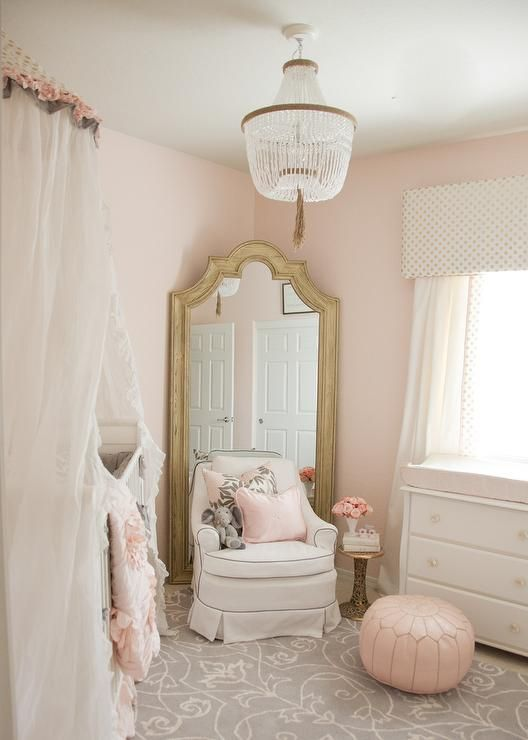 A PB Kids Rissa crystal beaded chandelier illuminates a whimsical pink and gray girl's nursery design featuring a white crib accented with a stunning sheer white canopy while a white skirted glider with gray piping sits on a gray and white area rug in front of a gold French nursery floor mirror positioned caddy corner against light pink walls. Beside the glider, a gold pedestal side table is placed behind a pink Moroccan leather pouf sat in front of a white dresser boasting a light pink…