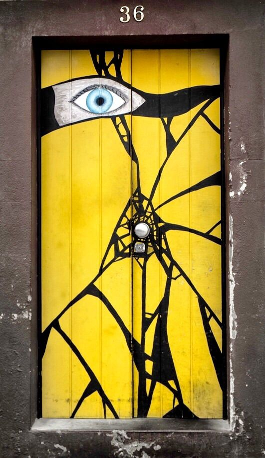 Funchal, Madeira, Portugal door  ~~  Yellow with black cracks and blue eye.