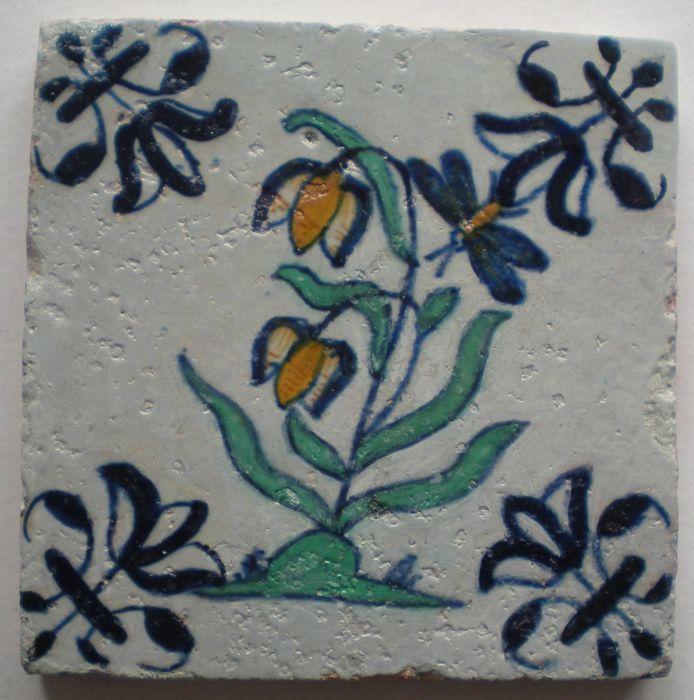 Antieke tegel met een polychrome bloem  ( zeldzaam) Hoekmotief bijzondere lelie Conditie gerestaureerd Maat ca 13x13x1,2 cm  GEEN BREUK !