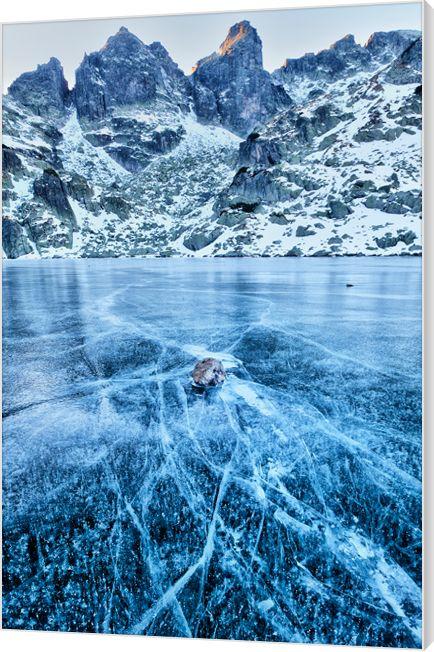 Frozen lake. Winterse foto van een bevroren meer. De barsten in het ijs zijn haarscherp vastgelegd voor een spectaculair effect. Luxe wanddecoratie van Wallstars.