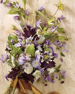 """Peak Season: Spring, summer, early fallBell-shaped clematis has a trailing shape that can help create glorious cascading bouquets and floral crowns. Plus, says Owen, """"the leaves bring in a nice touch of greenery."""" She included passion vines, scabiosas, heuchera foliage, dusty miller, and spray roses to create a loose, sweeping clutch."""