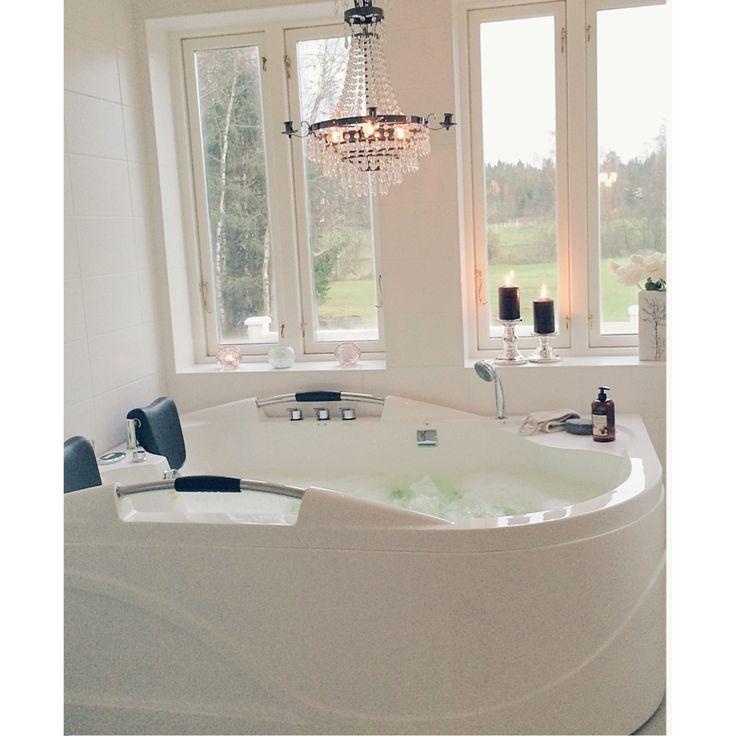 Badrum med badkar med utsikt över vår stora gård. Vackert med kristallkrona över badet.