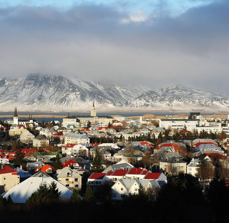 Iceland sky snow Winter mountainous landforms mountain cloud Town mountain range City rural area tree hill Village fell landscape freezing suburb house panorama place of worship