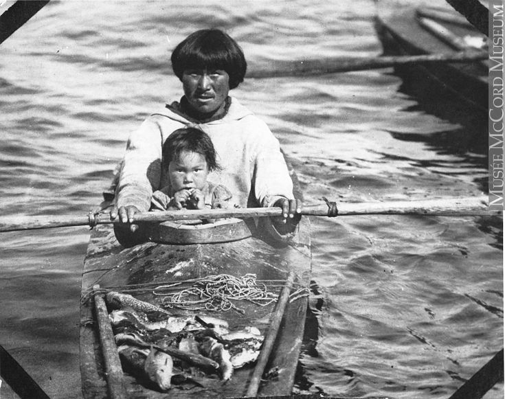 nuit man and children in kayak, Port Harrison, QC, about 1920