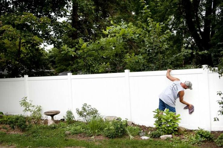 Lemieux Fence Co. employee Bill Ade cleans up a vinyl fence that was just installed at a Midland home on Thursday. Vinyl fences cost more and can last for many year. Wood fences are more popular mainly because that they can cost half of what vinyl fences cost. Photo: NICK KING | Nking@mdn.net