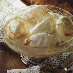 Oeufs à la Neige - literally 'eggs in the snow' or île flottante (floating island) is meringue floating in crème anglaise (a vanilla custard). Spun caramelized sugar virtually hovers seductively on top. A light fluffy, oh so French dessert - c'est tres delicieux!
