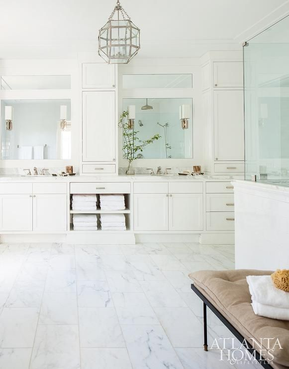 Scout for The Home - Luxurious large white master bathroom features a Suzanne Kasler Morris Lantern hung above staggered marble floor tiles leading to a white his and hers washstand boasting white cabinets flanking towel shelves and white marble countertops fitted with oval sinks positioned beneath inset mirrors illuminated by brass sconces placed on either side of inset white cabinets.