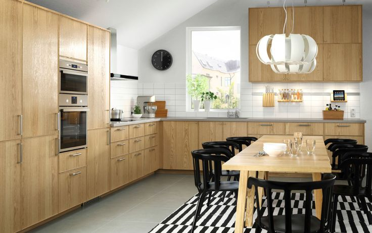 An oak kitchen with stainless steel appliances combined with black chairs and an oak dining table.