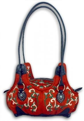 """Debi- Debi lives up to the expression, """"Orange is the new black."""" Loaded with attitude! Dark orange suede with black leather accents. Lovely floral embroidery. Bottom has four molded feet. Lined in teal peau de soie. Two open pockets and one zippered pocket. Zipper closure. $75.00 http://oatcouture.wazala.com/products/?page=2"""