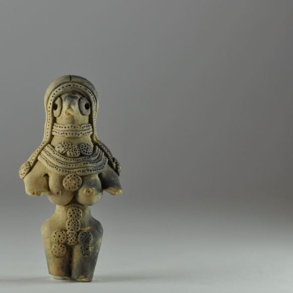 Insus Valley Mehrgarh female figurine, 3500-2000 B.C.  Highly decorated, she is wearing a headdress, a choker, and a necklace above her exposed breasts, circular decoration is scattered around her body including between her breasts and over her genitalia, broken off at the legs, 7.4 cm high. Private collection