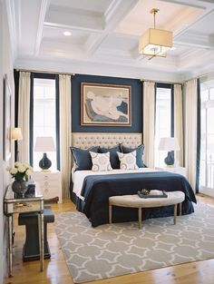 Navy blue and cream are delicious in this chic bedroom. Also check out the unconventional rug placement!