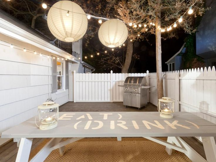 A white privacy fence encloses this backyard patio while still allowing the space to feel open  String lights and paper lanterns provide soft outdoor lighting above a painted picnic table and stainless steel grill
