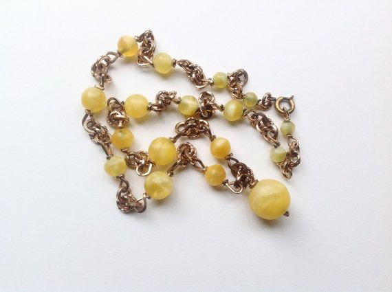 Vintage, Art Deco, golden yellow, opaque glass and fancy rolled gold chain necklace. This necklace has a very decorative design with the thick rolled gold links being used imaginatively. The necklace is in good vintage condition. Three of the small beads have small chips near the beading holes. I believe the ring bolt clasp to be a replacement clasp which is from a similar era. The rolled gold wires are a good colour. The length of the necklace is 17 inches or 43 cm approximately.