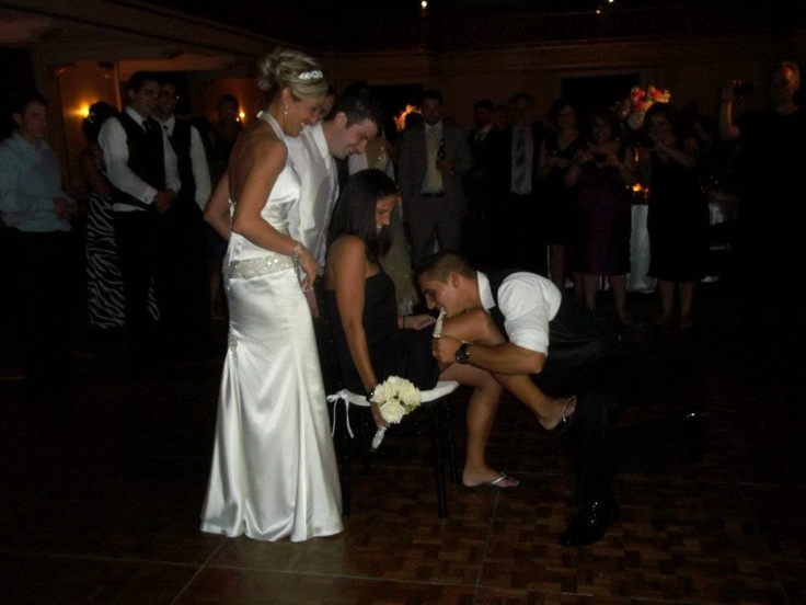 At their wedding reception, a bride and groom keep an eye on a groomsman, who uses his teeth to put the garter on the leg of the female wedding guest who caught the bride's bouquet. The couple did a traditional toss for their single guests. The bride, laughing, is stunning in a sleek satin halter gown with a beaded drop waist. The John Parker Band added music and dancing to the party, held at the Omni William Penn Hotel in Pittsburgh. http://www.jpband.com/weddings.html