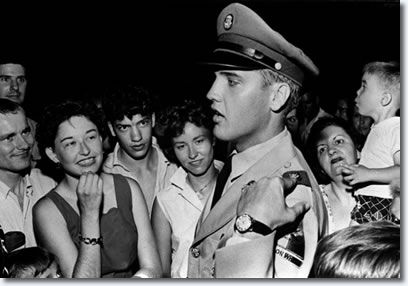 Elvis Presley explains the insignia on his uniform to fans at the gates of Graceland Sunday evening June 1, 1958. Elvis arrived late Saturday night for a two week leave. He was inducted into the army at Memphis March 24, 1958.