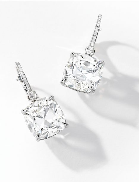 Pair of Diamond Earrings:  Each suspending a cushion-shaped diamond weighing 10.82 and 10.42 carats respectively, to a diamond-set hook surmount, mounted in 18 karat white gold.   Via Sotheby's.