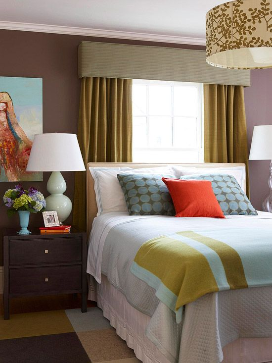 Visual Trick  In the master bedroom, the only spot for the couple's queen-size bed was under a narrow window. A valance and draperies add 8 inches to either side of the window, making it appear wider than the bed and giving the space balance.