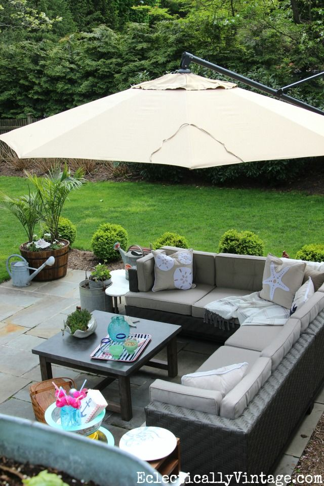 Beautiful patio makeover - love the outdoor sectional and the concrete topped coffee table and the offset umbrella not to mentio her gorgeous planters kellyelko.com