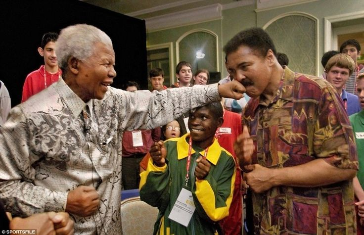 """Two giants: Former South African President Nelson Mandela lands a """"straight left"""" to the chin of former World Champion Muhammad Ali as South African Special Olympics Athlete Rofhiwa looks on in June 2003"""