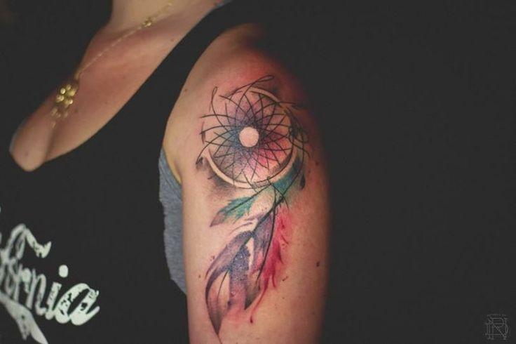 un bel attrape-rêves avec plumes multicolores tatoué sur le bras