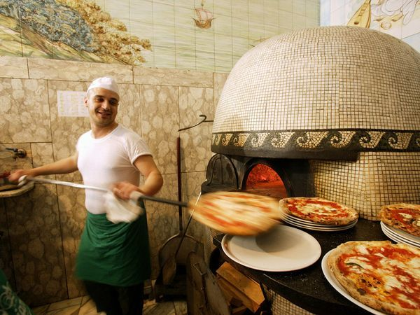 Naples Pizzeria  Photograph by Borchi Massimo/4Corners Images    Following the arrival of South American tomatoes in the early 16th century, Naples became the home of the first pizzeria, originating the idea of individual pies cooked to order. Italian foodies don't limit their toppings to simple sauce and cheese, with local favorites including the napoletana, cheese topped with capers and anchovy, or patate con rosamarino, sliced potatoes and rosemary.
