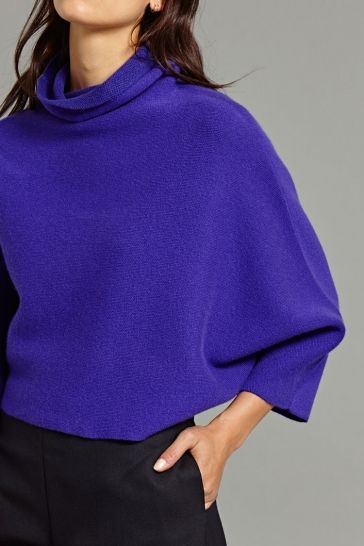 Fio Cashmere Pullover in Purple and Bright Navy - This cashmere pullover is cropped to above the waist to create a layered silhouette within an outfit. It features a high neck and batwing sleeve construction.