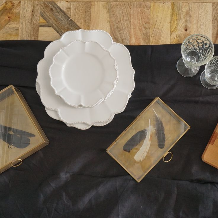 Sauvage Interiors industrial dining with selection of French scalloped plates, brass and glass boxes and La Rochère glassware #industrialdining #parquetrytable #scallopedplates #brassboxes #larochereglasses