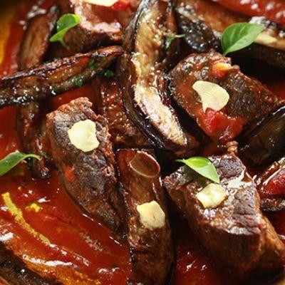 Ζεσταίνουμε μια κατσαρόλα σε μέτρια προς δυνατή φωτιά , ρίχνουμε το μισό ελαιόλαδο (100 γρ) και τηγανίζουμε τις μελιτζάνες μέχρι να πάρουν έντονο χρυσαφένιο χρώμα και να μαλακώσουν.