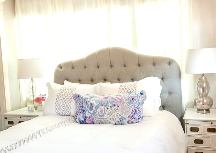 Off center windows behind bed disguised by entire wall of airy white curtains