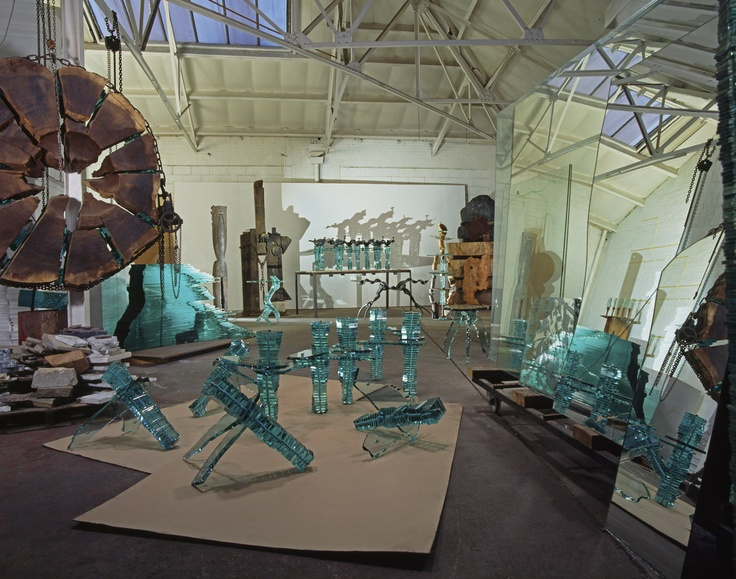 This photo was taken in Danny Lane's studio by Peter Wood in 1996? The hanging wooden sculpture is a  6 ft diameter slice of cedar of Lebanon was burned through and divided into 12 sections and restructured like an Roman arch. Glass sculpture components and glass furniture components are scattered around Danny Lane's studio.