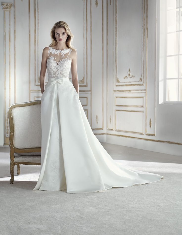 PROSPERA – LA SPOSA 2018 Spectacular wedding dress that combines two looks. On the one hand, the low-waist satin mermaid silhouette with lace appliqués is paired with a detachable overskirt, also in satin and embroidered lace with beading. And on the other hand, the marvelous bodice combines a bateau neckline on the front with illusions...  Citește mai mult »