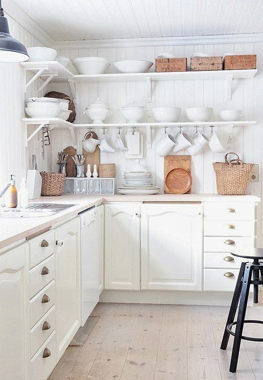 A mix of seagrass and wicker baskets adds an earthy warmth to this all-white kitchen.