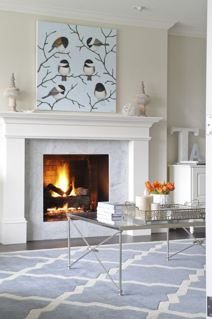 Living Room designed by Enviable Designs - This fireplace is tiled with a Carrera marble surround and white mantle, upon which perches a whimsical style piece of art.
