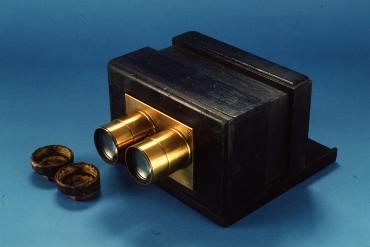 A stereoscopic wet plate camera. The body of the camera consists of a wooden box that has been painted black. There are two brass lenses attached to the front of the camera. The lenses can be individually unscrewed and removed. A removable wooden framed glass plate slides down the back of the camera. A pair of lens caps made from wood and velvet lined leather fit over the camera lenses.: Lens Camera, Brass Lenses, Stereo Lens, Wet Plates, Camera Consistency, Camera Crazy, Plates Camera, Camera Lens, Glasses Plates