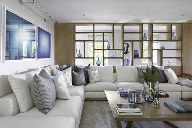 Sala de estar tem cores claras, detalhes azuis e estante de madeira vazada usada como divisória. Projeto do escritório Workshop APD