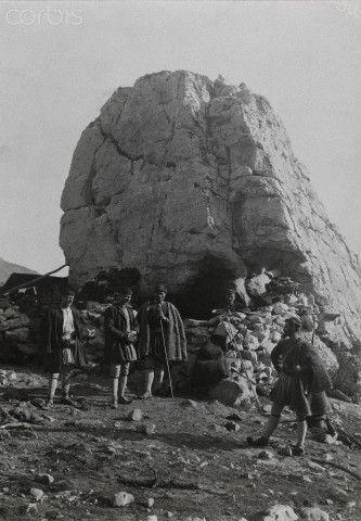 Five men gather beside a giant boulder on Mount Parnassus-Fred Boissonnas