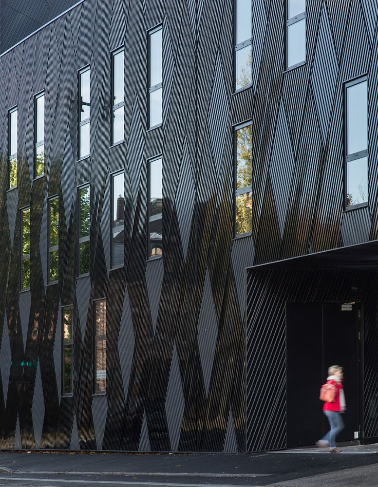 Black, striated metal panels cover the extension that Gautrand designed to accompany her curved concrete drama centre in French city Béthune. The dark cladding complements the glossy purple varnish and black diagonal details that cover its neighbour.